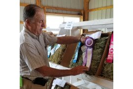 Pennsylvania Hay Show judge, Les Vough, places the Section I Grand Champion ribbon on the winning hay sample. Photo: Jessica Williamson, Penn State Extension