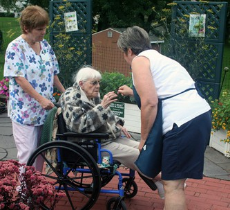 A senior center resident enjoys a garden tour and a freshly picked raspberry from our gardens!